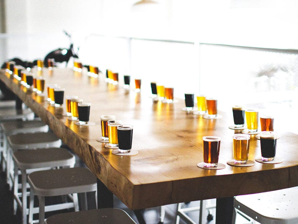 microbreweries long table with shots tasting draft beer blond red dark brew 33 Acres Brewing Company vancouver british columbia canada ulocal local products local purchase local produce locavore tourist