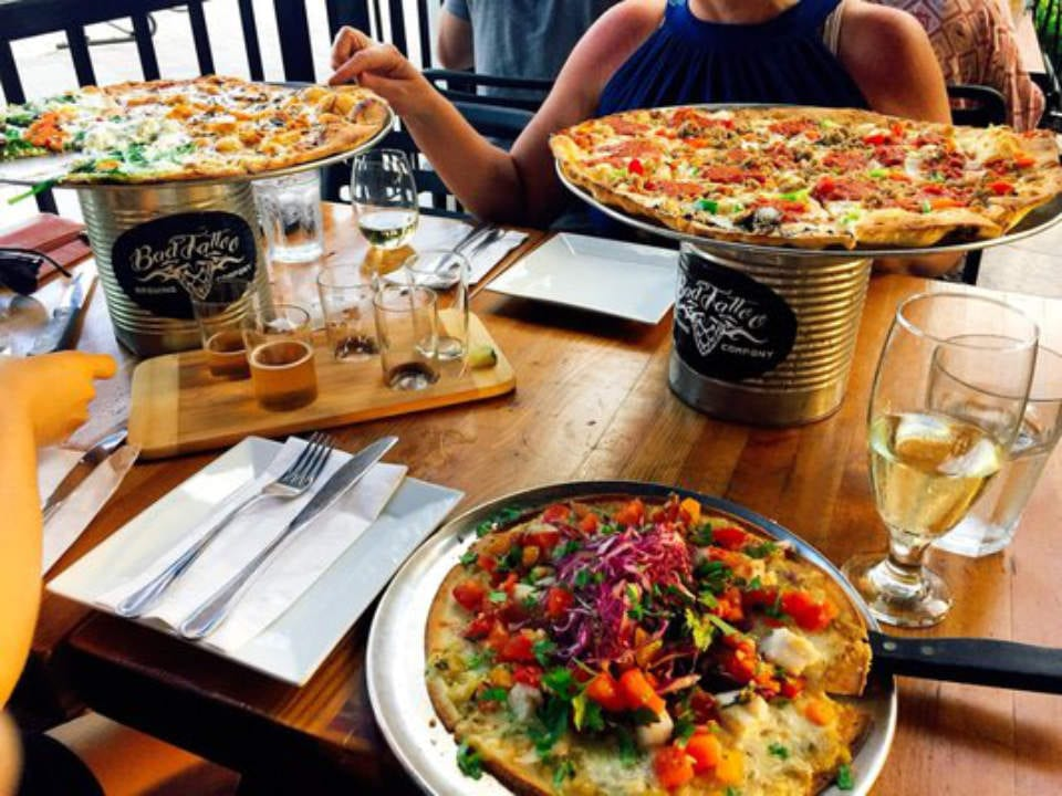 microbreweries tasting draft beer plate 3 pizzas on a can wood table bad tattoo brewing penticton british columbia canada ulocal local products local purchase local produce locavore tourist