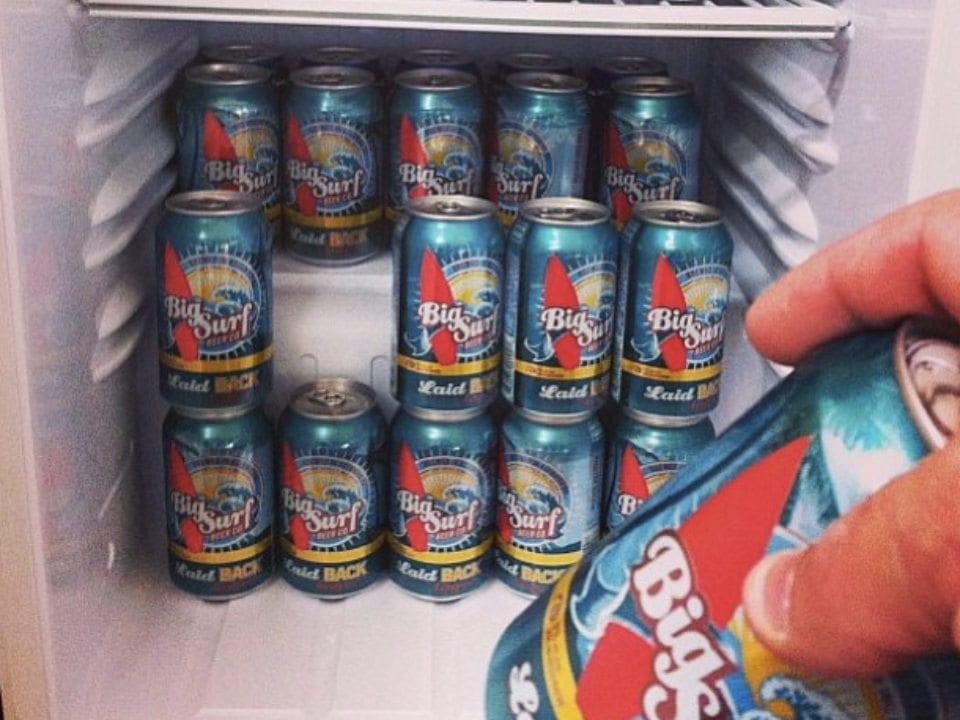 microbrasseries main qui place une cannette de bière dans réfrigérateur remplie de cannettes bière artisanale big surf beer co kelowna colombie britannique canada ulocal produits locaux achat local produits du terroir locavore touriste