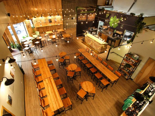 microbreweries taproom seen from above several tables and chairs in wood with tasting bar on the side devil's club brewing co juneau alaska united states ulocal local products local purchase local produce locavore tourist