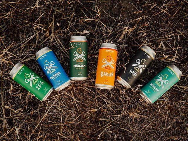 microbrasseries 5 cannettes de bière artisanale de différente sortes sur le gazon district brewing co regina saskatchewan canada ulocal produits locaux achat local produits du terroir locavore touriste