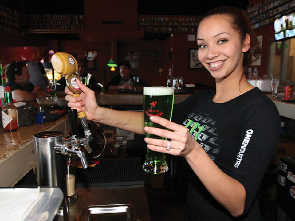 microbreweries bartender chantelle vaudry holds up green beer left over drummond brewery red deer alberta canada ulocal local products local purchase local produce locavore tourist
