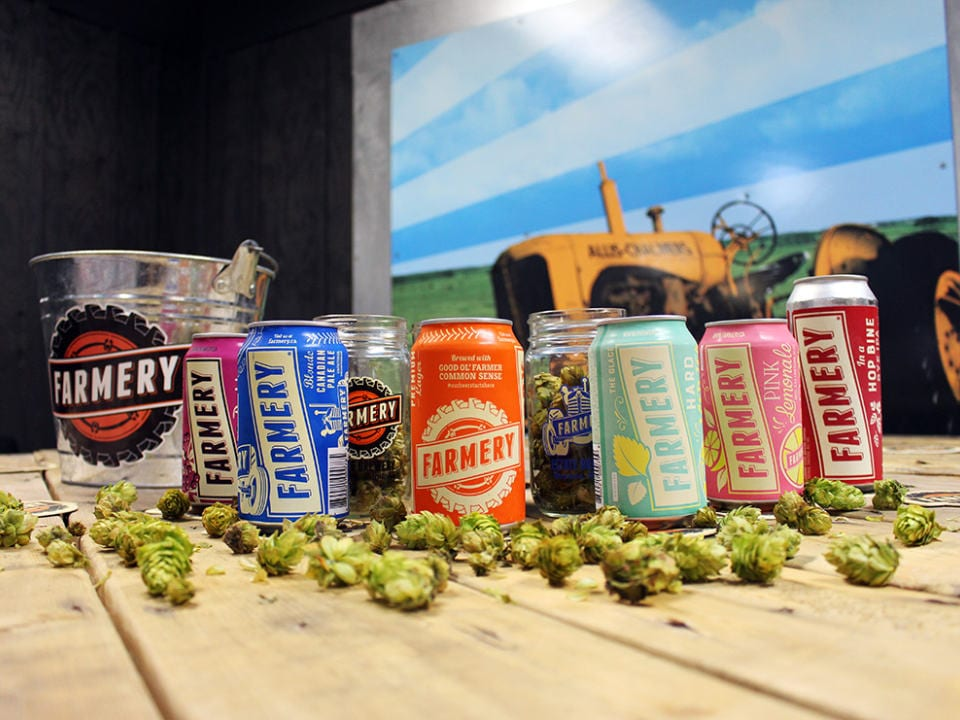 microbreweries cans of craft beer with fresh hops and yellow tractor in background farmery estate brewery neepawa manitoba canada ulocal local products local purchase local produce locavore tourist