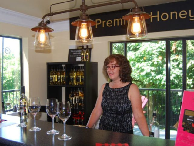 vineyard owner of the vineyard behind the tasting bar ready to show her wine festina lente estate winery langley british colombia canada ulocal local products local purchase local produce locavore tourist