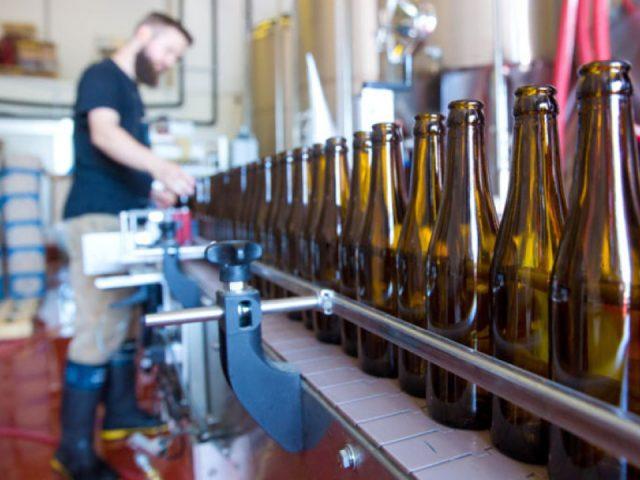 microbrasseries homme debout usine de fabrication bière artisanal série de bouteilles four winds brewing co delta colombie britannique canada ulocal produits locaux achat local produits du terroir locavore touriste