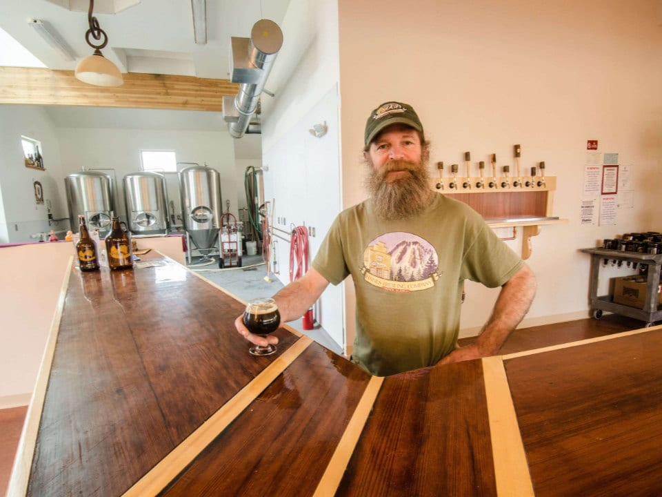microbreweries owner at tasting bar with view of manufacturing plant in the back of the room haines brewing company inc haines alaska united states ulocal local products local purchase local produce locavore tourist