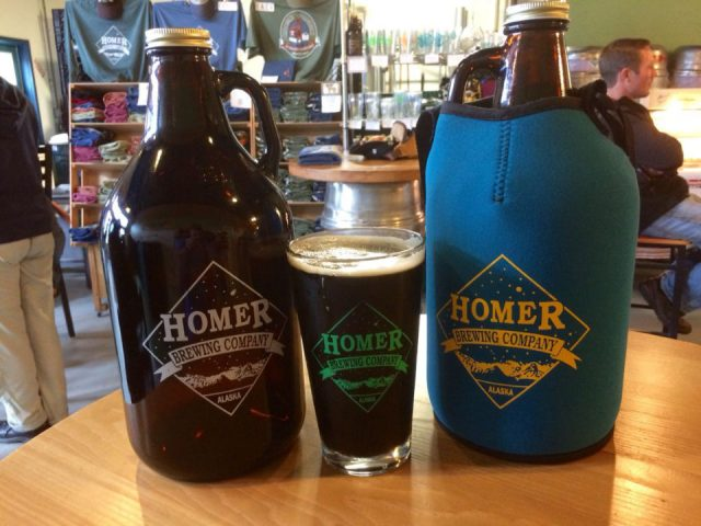 microbreweries 2 growlers with a glass of artisanal brown beer between on a table in the tasting room and shop with customers in the back homer brewing company homer alaska united states ulocal local products local purchase local produce locavore tourist