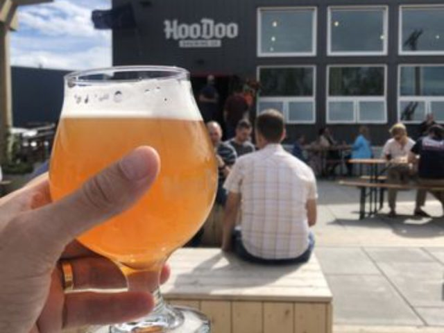 microbreweries hand holding a glass of craft beer with terrace and brewery building in the background hoodoo brewing company fairbanks alaska united states ulocal local products local purchase local produce locavore tourist
