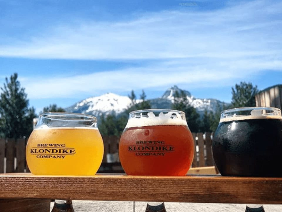 microbreweries flights of 3 glasses of craft beer with rocky mountains in the background klondike brewing company skagway alaska united states ulocal local products local purchase local produce locavore tourist