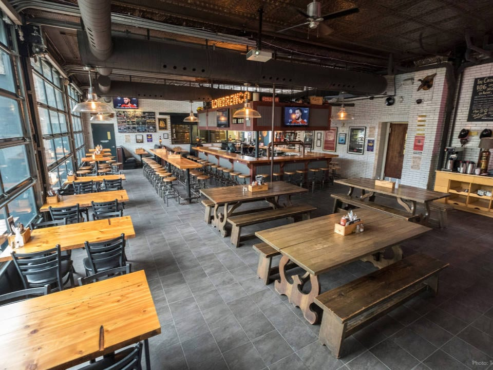 microbreweries taproom in old fire station with wooden tables and chairs and large tasting bar in the center lake of the woods brewing company kenora ontario canada ulocal local products local purchase local produce locavore tourist
