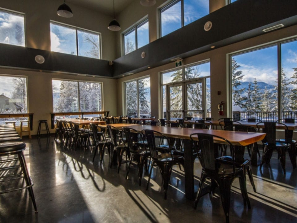 microbreweries tasting room with tables and chairs window view trees and mountain mt begbie brewing co revelstoke british columbia canada ulocal local products local purchase local produce locavore tourist