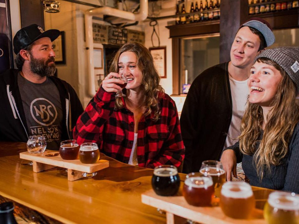 microbreweries 4 people sitting at the tasting bar with a tasting board of craft beers nelson brewing company nelson british colombia canada ulocal local products local purchase local produce locavore tourist