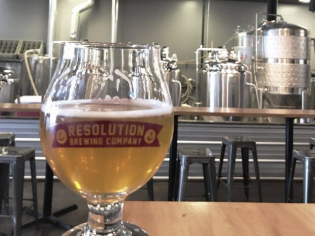 microbreweries glass of craft beer on a table in the tasting room with craft beer factory in the background resolution brewing company anchorage alaska united states ulocal local products local purchase local produce locavore tourist