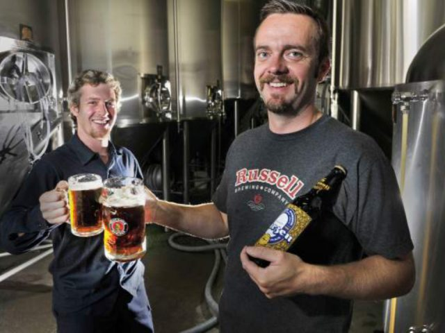 microbreweries employee justin white and head brewer jack bensley hoist a pint marzen beer russell brewing company surrey british columbia canada ulocal local products local purchase local produce locavore tourist