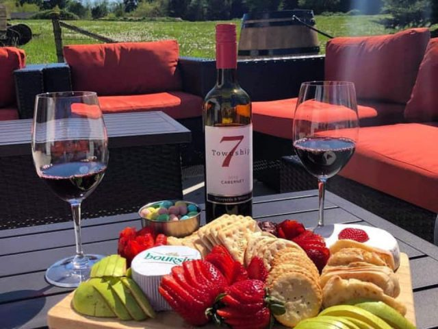 vineyard terrace with red couches and plate of fruit cheeses cookies on black table with 2 glasses of red wine and a bottle township 7 vineyards and winery langley city british colombia canada ulocal local products local purchase local produce locavore tourist