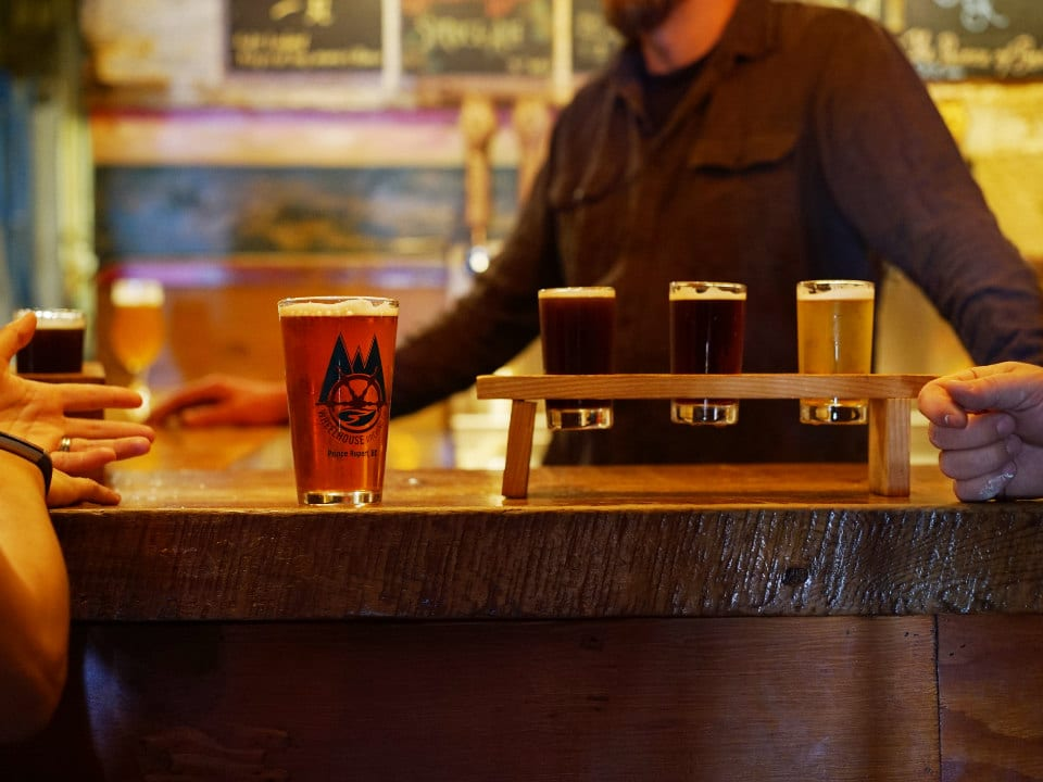 microbreweries tasting palette of craft beer and a glass of craft beer on the bar with bartender in the background wheelhouse brewing co prince rupert british columbia canada ulocal local products local purchase local produce locavore tourist