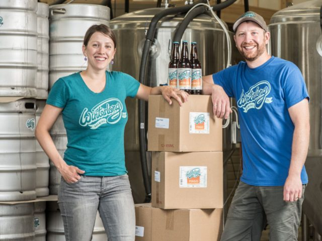 microbreweries marko and meghan marjanovic 2 master brewer owners in manufacturing plant with crates of craft beer in bottles winterlong brewing co Whitehorse yukon canada ulocal local products local purchase local produce locavore tourist