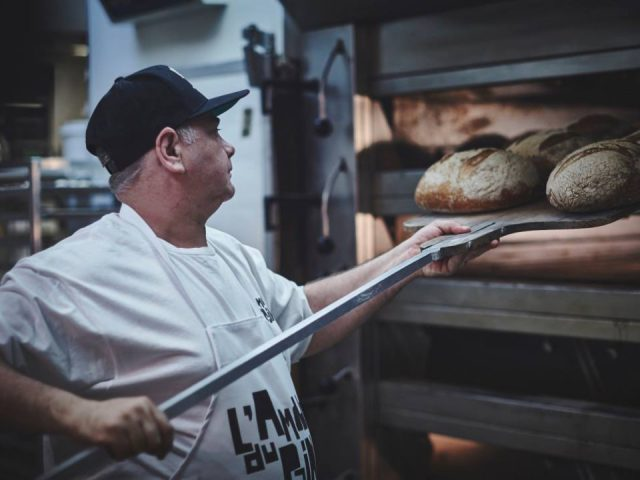 artisan bakeries baker who takes out the buns from the oven l'amour du pain griffintown montréal quebec canada ulocal local products local purchase local produce locavore tourist