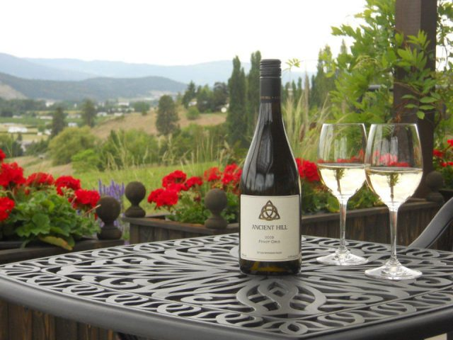 vineyard glass and bottle of white wine on a terrace table with nature in the background ancient hill estate winery kelowna british colombia canada ulocal local products local purchase local produce locavore tourist