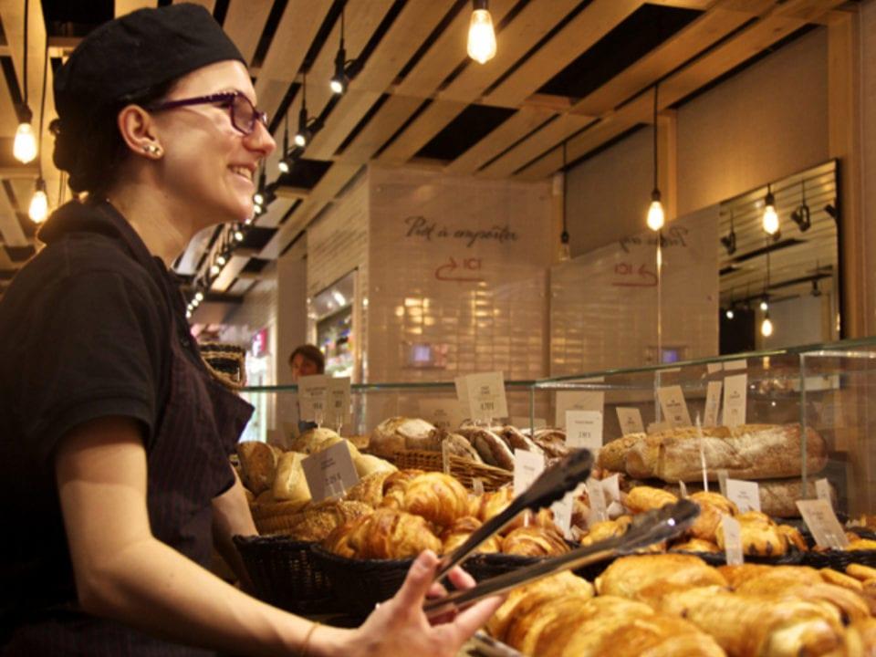 boulangerie artisanale employée qui est au comptoir de patisseries prête à servir les clients au pain doré côte-des-neiges montréal québec canada ulocal produits locaux achat local produits du terroir locavore touriste