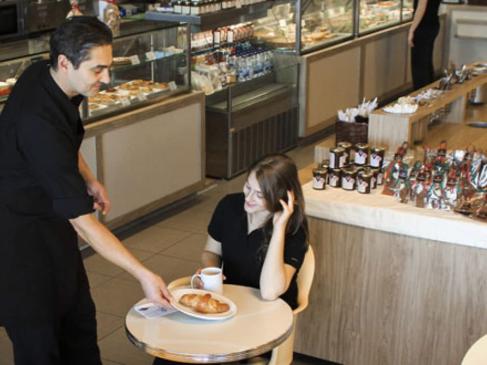 artisan bakeries employee serves a croissant to a customer at her table with the pastry display stands around them au pain doré de l'avenir laval quebec canada ulocal local products local purchase local produce locavore tourist