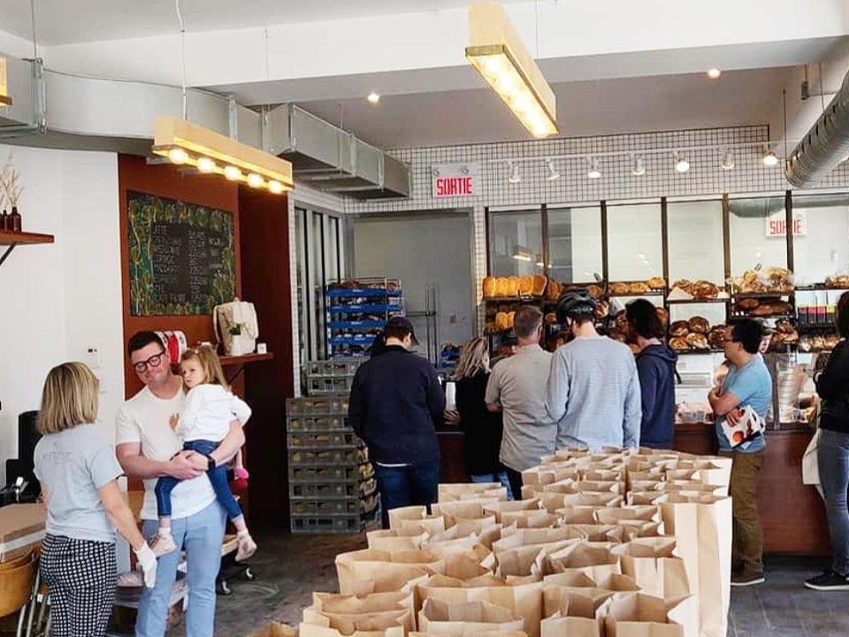 boulangerie artisanale intérieur de la boulangerie avec table remplie de sacs pour mettre les commandes avec plusieurs clients devant les présentoirs des patisseries automne boulangerie montréal québec canada ulocal produits locaux achat local produits du terroir locavore touriste