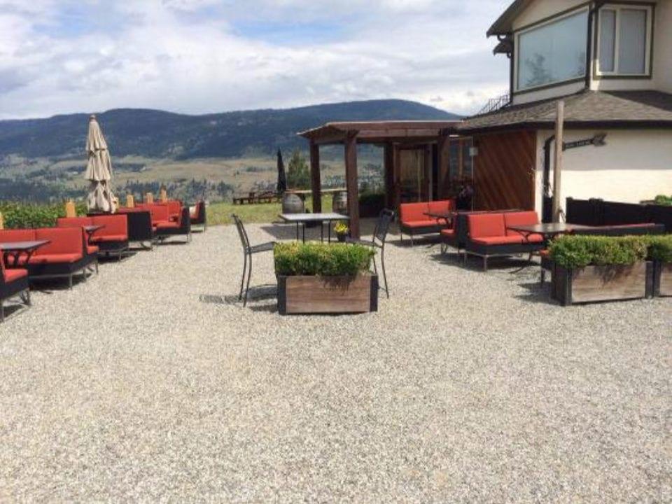 vignoble grand patio avec banquettes rouge et tables avec vue du haut du vignoble blind tiger vineyards lake country colombie britannique canada ulocal produits locaux achat local produits du terroir locavore touriste
