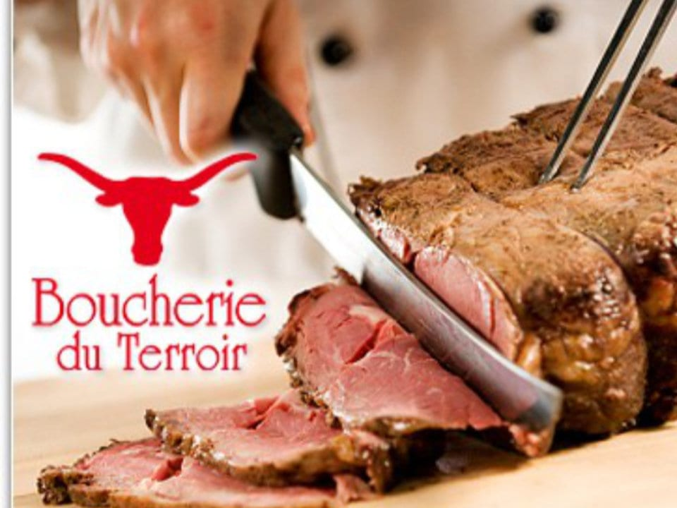 butcher shop butcher cutting a slice of meat in a roast beef boucherie du terroir chambly quebec canada ulocal local products local purchase local produce locavore tourist