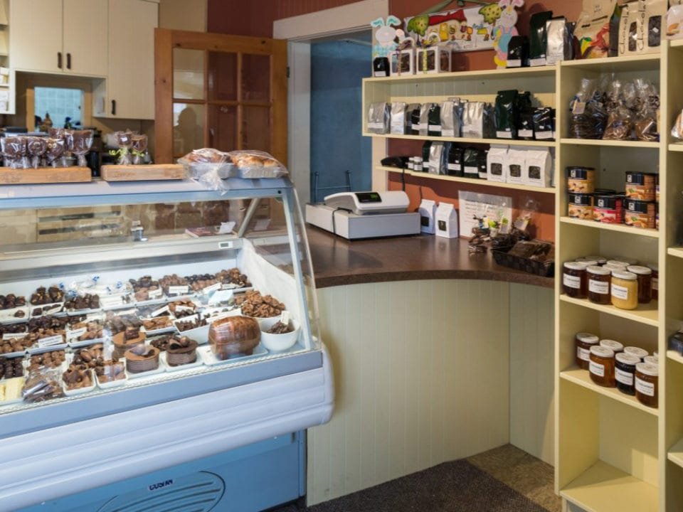 artisan bakeries shop interior with refrigerated counter and shelves filled with homemade products boulangerie chartrand saint-antoine-abbé quebec canada ulocal local products local purchase local produce locavore tourist