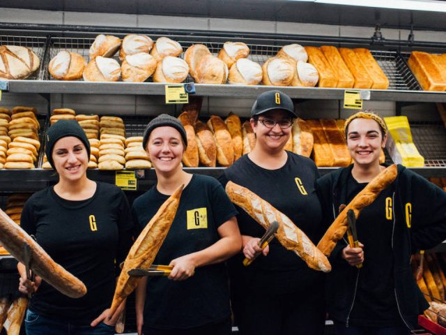 artisan bakeries employees who are smiling with baguette in their hands and wall of bread of the day behind them boulangerie guillaume montréal quebec canada ulocal local products local purchase local produce locavore tourist
