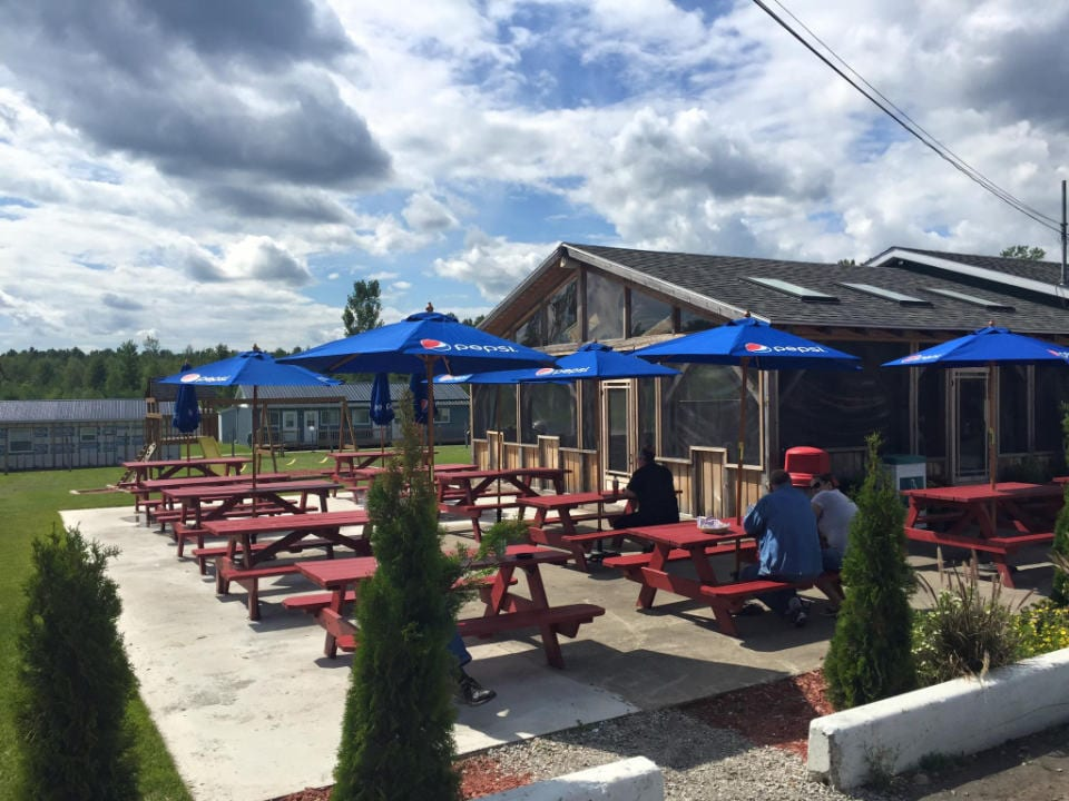 restaurant large terrace with picnic tables and umbrellas with guests burger bob hemmingford quebec canada ulocal local products local purchase local produce locavore tourist