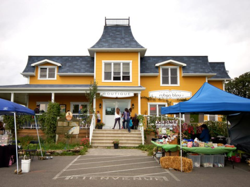cheese factories big yellow ancestral house of the cheese factory and shop with kiosk outside in the parking lot fromagerie ruban bleu mercier quebec canada ulocal local products local purchase local produce locavore tourist
