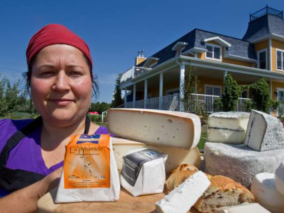 cheese factories owner and cheesemaker caroline presents her cheese on a tray outside of the boutique in the background fromagerie ruban bleu chateauguay quebec canada ulocal local products local purchase local produce locavore tourist