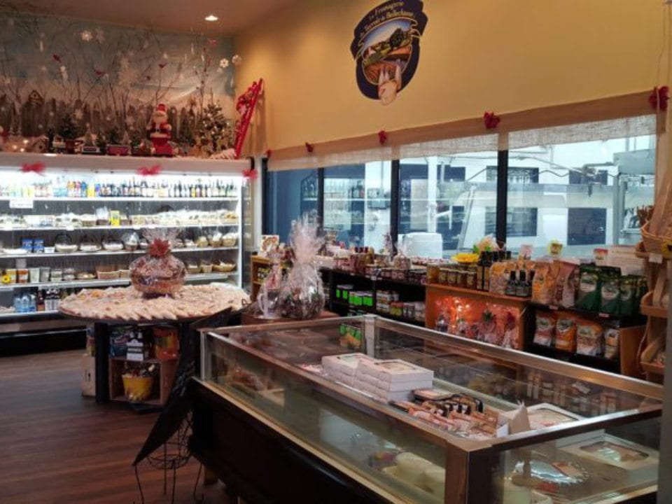 cheese factories interior of the shop with several prepared food pies refrigerated counter and view of the cheese dairy by the glass wall fromagerie du terroir de bellechasse saint-vallier quebec canada ulocal local products local purchase local produce locavore tourist