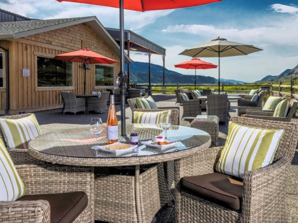 vineyard large patio with plenty of seating overlooking the winery and glasses and bottle of rosé on a table with plate of cheeses and crackersharper's trail estate winery kamloops british colombia canada ulocal local products local purchase local produce locavore tourist