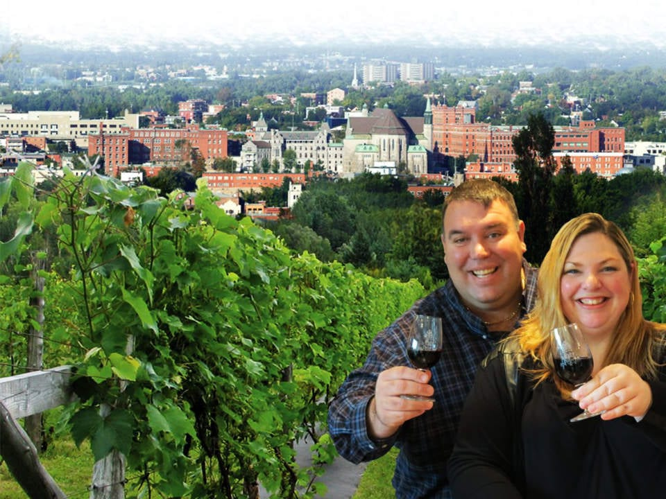 vineyard couple owning vineyard with a glass of red wine in their hands view of vineyard and city in the background la halte des pèlerins sherbrooke quebec canada ulocal local products local purchase local produce locavore tourist
