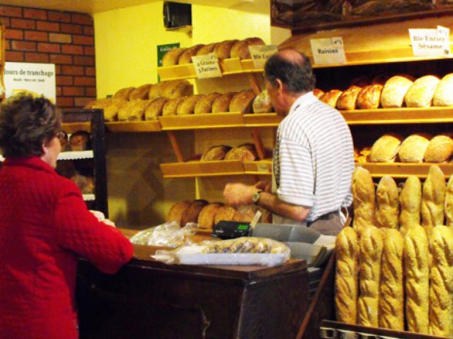 artisan bakeries jean-claude reinbold helps a customer at the counter with breads on the shelves la mie de la couronne sherbrooke quebec canada ulocal local products local purchase local produce locavore tourist