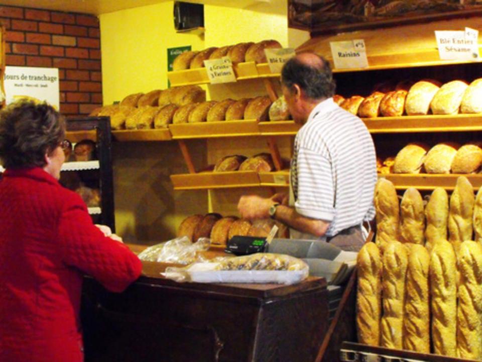boulangerie artisanale jean-claude reinbold aide une cliente au comptoir avec les présentoires de pains sur les tablettes la mie de la couronne sherbrooke québec canada ulocal produits locaux achat local produits du terroir locavore touriste