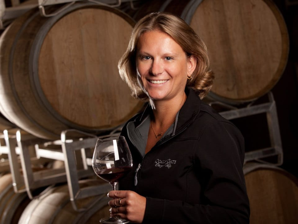 vineyard winemaker nikki callaway surrounded by cedar barrels with a glass of red wine in her hands laughing stock vineyards penticton british colombia canada ulocal local products local purchase local produce locavore tourist