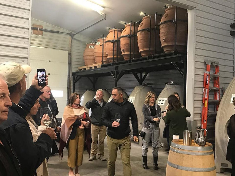 vineyard guided and tasting tour with customers in the wine aging room filled with cedar casks laughing stock vineyards penticton british colombia canada ulocal local products local purchase local produce locavore tourist