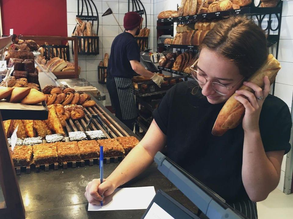 boulangerie artisanale commande par téléphone employée fait une imitation de téléphone avec une baguette de pain et comptoir de pains et patisseries du jour le pain dans les voiles mont-st-hilaire mont-saint-hilaire québec canada ulocal produits locaux achat local produits du terroir locavore touriste