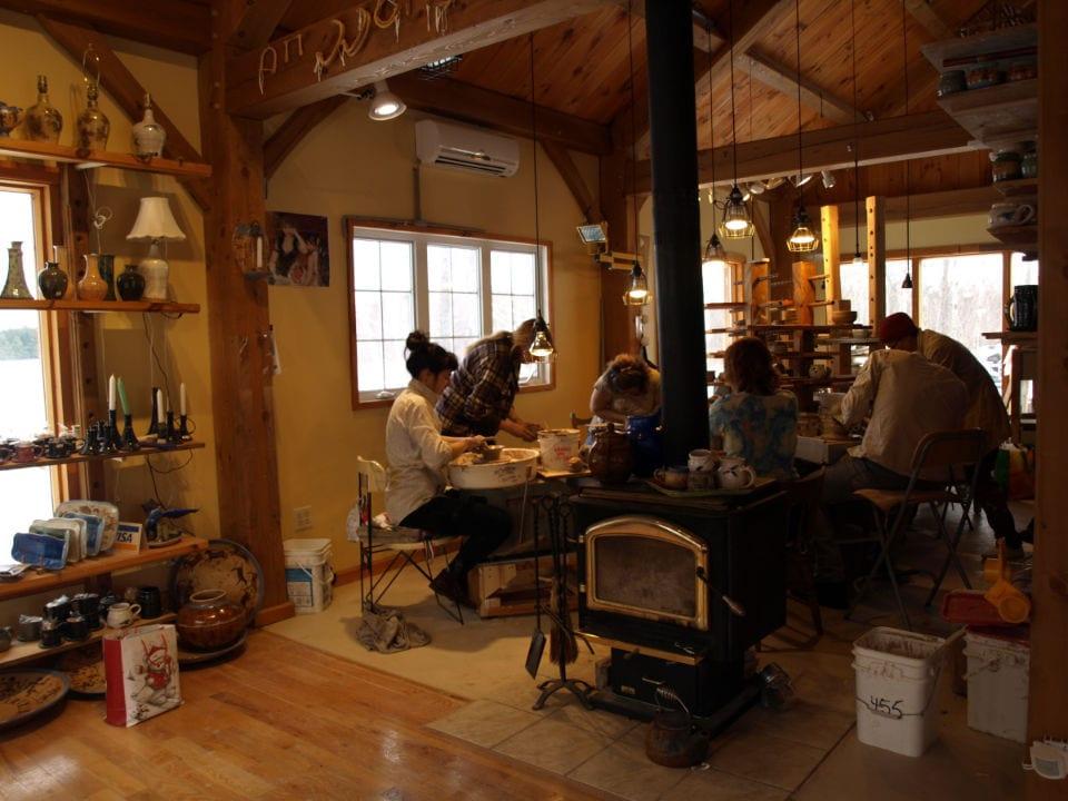 artisans étudiants assistent à un cours de poterie donné par ronald pothierà côté du poèle à bois le potier pothier havelock québec canada ulocal produits locaux achat local produits du terroir locavore touriste