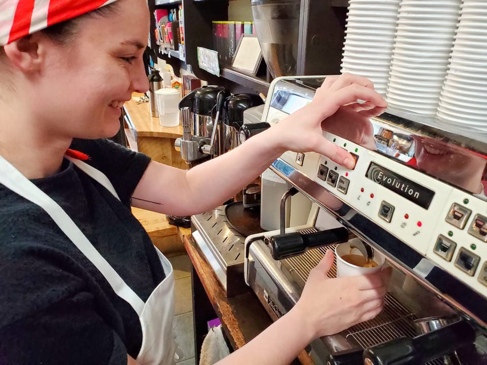 artisan bakeries employee at the coffee machine for a regular coffee latte an american espresso or cappuccino with a smile les co'pains d'abord rachel montréal quebec canada ulocal local products local purchase local produce locavore tourist