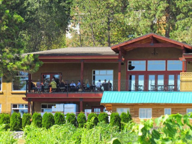 vineyard view of the 2-storey building and terrace with guests enjoying the sun little straw vineyards west kelowna british colombia canada ulocal local products local purchase local produce locavore tourist