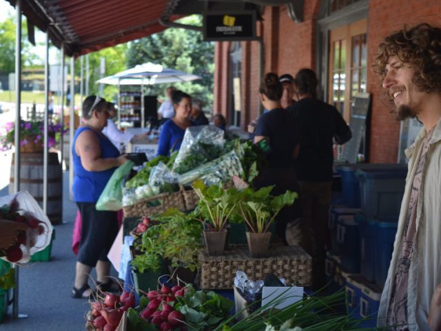 public markets kiosk outside of local fruit and vegetable traders with customers walking around marché de la gare de sherbrooke sherbrooke quebec canada ulocal local products local purchase local produce locavore tourist