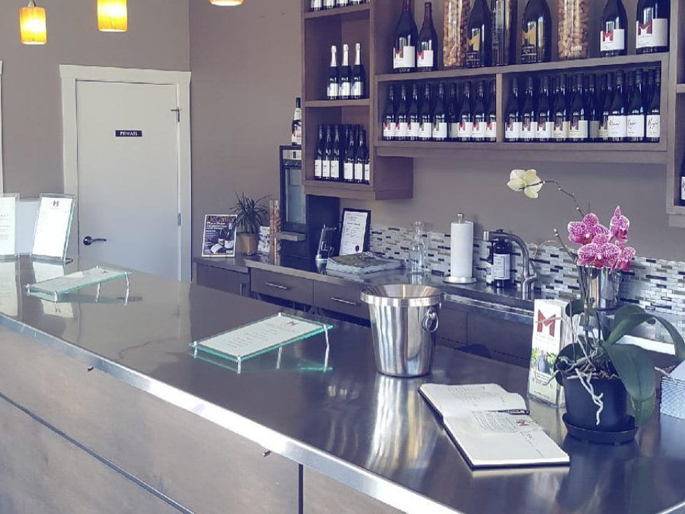 vineyard stainless tasting bar with bottles of wine on the back wall meyer family vineyards okanagan falls british colombia canada ulocal local products local purchase local produce locavore tourist
