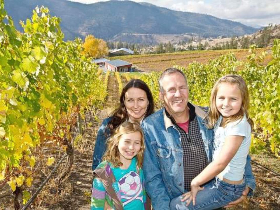 vineyard family owner in the vineyard with the building at the end of the road meyer family vineyards okanagan falls british colombia canada ulocal local products local purchase local produce locavore tourist