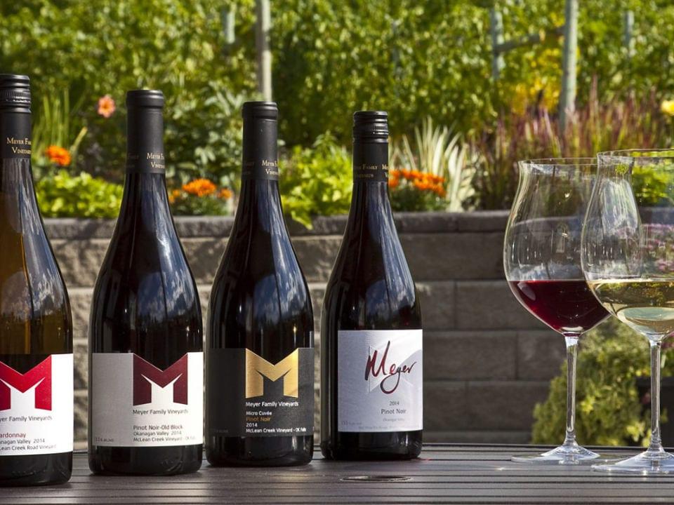 vignoble 4 bouteilles de vin variées de la maison avec 2 verres sur la table dehors sur le patio meyer family vineyards okanagan falls colombie britannique canada ulocal produits locaux achat local produits du terroir locavore touriste