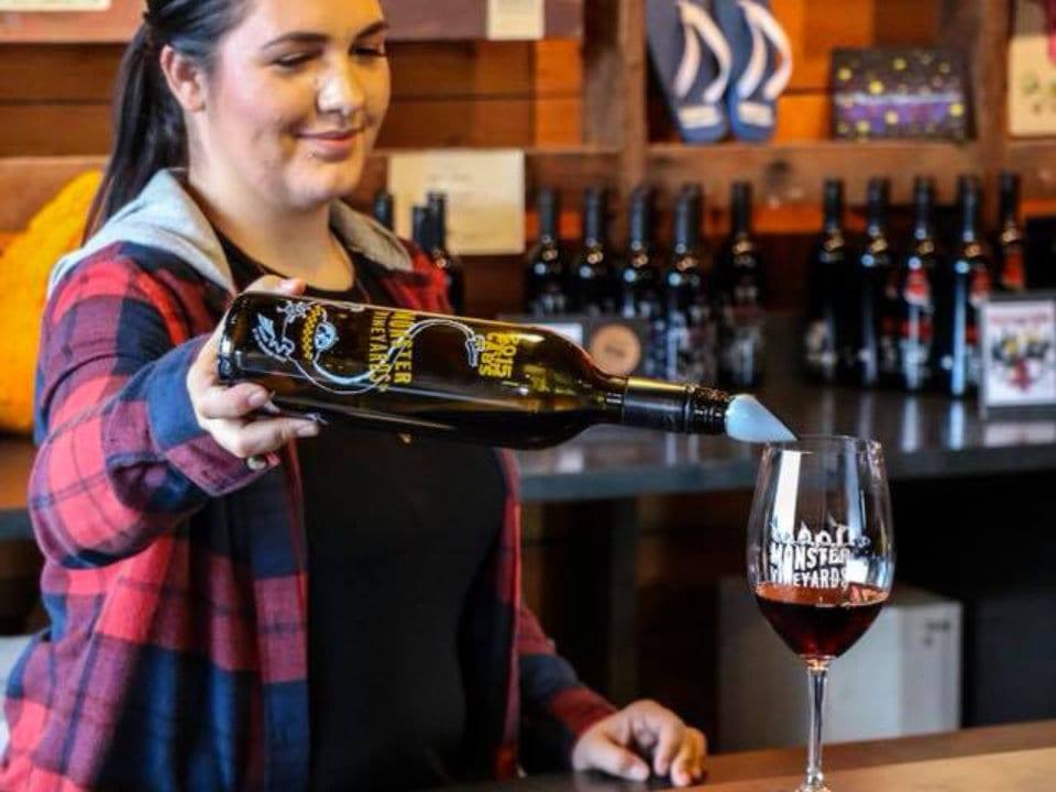 vignoble barmaid qui verse un verre de vin rouge pour une dégustation au bar monster vineyards penticton colombie britannique canada ulocal produits locaux achat local produits du terroir locavore touriste