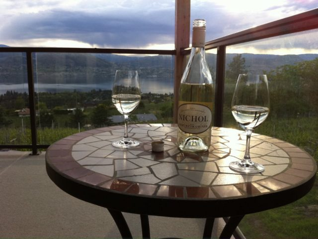 vineyard 2 glasses and a bottle of white wine on a table on the terrace with the vineyard and lake in the background nichol vineyard naramata british colombia canada ulocal local products local purchase local produce locavore tourist